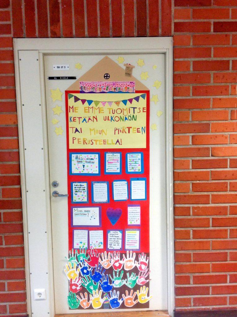 Oulun normaalikoulun 4 B:n tavoitetalo sijoitettiin luokan oveen, jotta oppilaat muistaisivat tavoitteensa aina luokkaan tullessaan. Kädenjäljet toimivat allekirjoituksena.