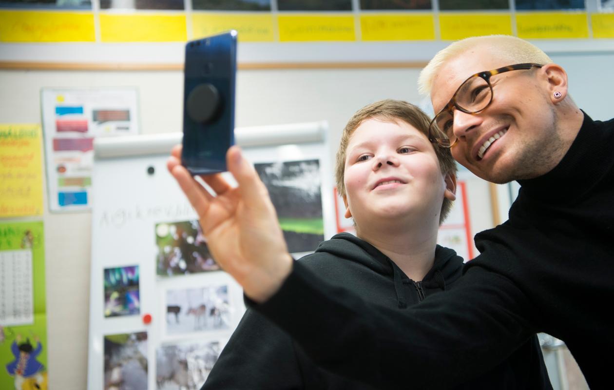 Antti Tuisku ottaa selfien oppilaan kanssa
